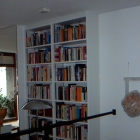 A bookcase in white melamine with bookcase strip in stainless steel to allow shelves to be adjusted (Barbican)