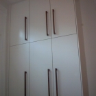 A full height wardrobe with plain doors and walnut bar handles      (New Cross)
