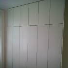 New wardrobes using up all of the wall with plain white touch doors  (Primrose Hill)
